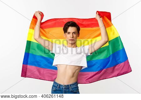 Young Man In Crop Top, With Glitter On Face, Raising Pride Flag With Confident Emotion. Queer Person