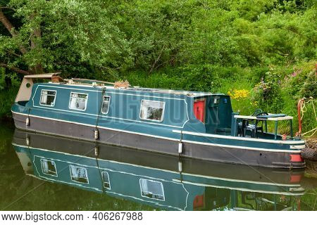 Narrowboat, british canal boat of traditional long and narrow design moored at the Kennet and Avon Canal in England, UK