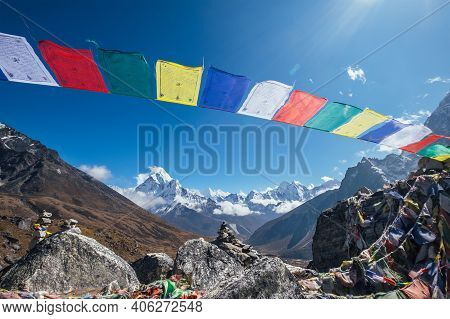 Holy Buddhist Praying Multicolored Flags With Mantras Flapping And Waving On The Strong Wind With Va