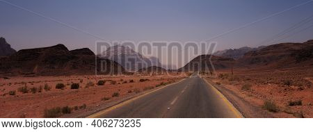 Long Deserted Road With The Mountains Of Wadi Rum In The Background