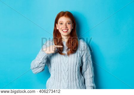 Beautiful Redhead Girl Pointing At Herself And Smiling Happy, Being Chosen, Standing In Sweater Agai