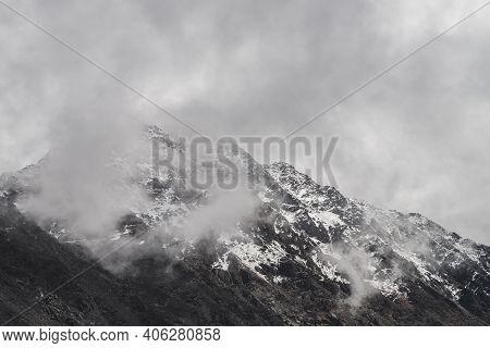 Atmospheric Minimalist Alpine Landscape With Snowy Rocky Mountain Peak. Low Clouds Near Snowbound Ra