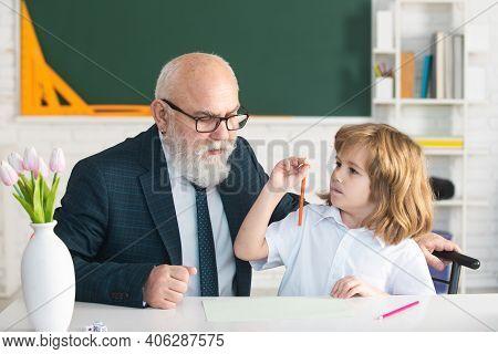 Teachering Concept. Help To Learn. Old Teacher With Schoolboy In Classroom. School Teacher, Educatio