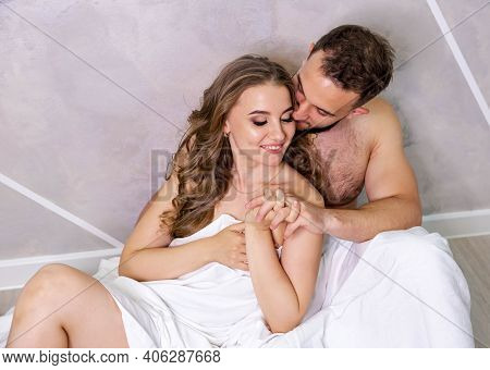 Young Sexy Couple In Love Sitting On The Floor, Embracing On White Sheets, Romantic Mood. Naked Coup