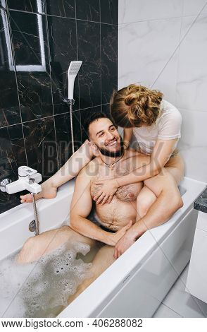 Sexy Couple Hugging And Kissing In Bath. Caucasian Couple Relaxing In Bathtub. Sensual Pair Kissing.