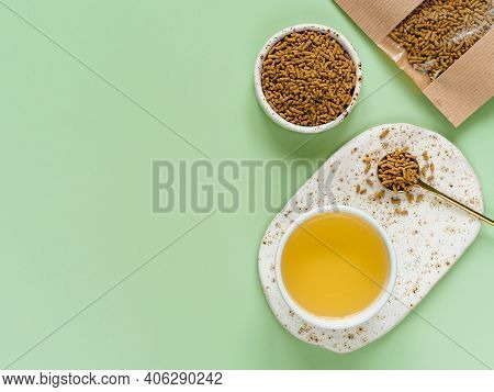 Cup Of Buckwheat Tea On Light Green Background. Top View Of Healthy Soba Tea And Groats Of Tartary B