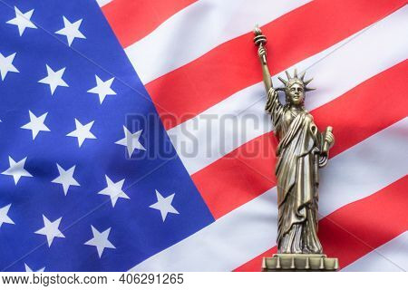 A Replica Of The Statue Placed On The Usa Flag. There Is Lighting On The Side Of The Statue. 4th Of