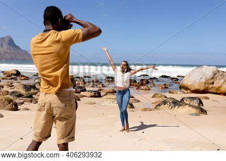 African american couple taking photos on a beach by the sea. healthy lifestyle, leisure in nature.