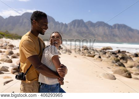 African american couple embracing on a beach by the sea. healthy lifestyle, leisure in nature.