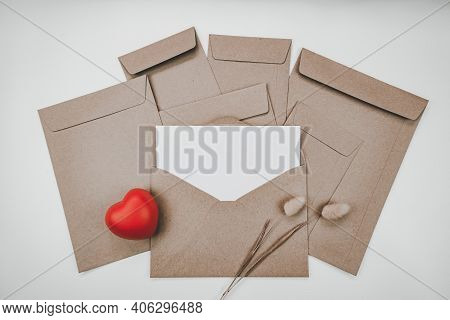 Blank White Paper Is Placed On The Open Brown Paper Envelope With Red Heart And Rabbit Tail Dry Flow
