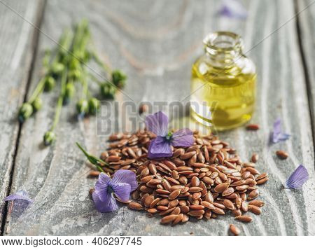 Flax Seeds And Flax Oil. Brown Linen Seeds, Flaxseed Oil And Blue Flax Flowers On Old Gray Wooden Ba