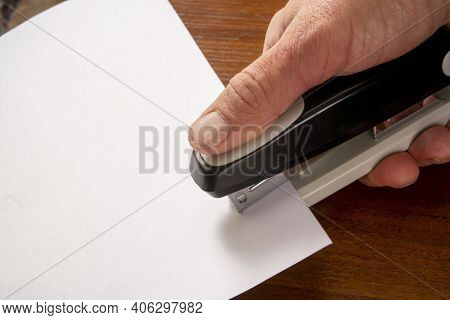 A Man Staples Together Several Sheets Of Paper With A Stapler