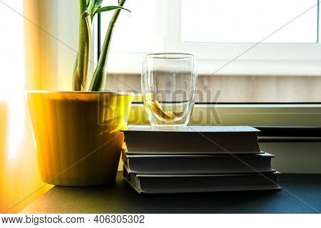 A Cup Of Hot Tea With Lemon Is On The Windowsill On A Pile Of Books, Steam Comes Out Of The Cup. Yel