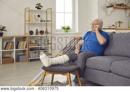 Senior Man With Leg Fracture Sitting On Couch At Home And Talking On Mobile Phone