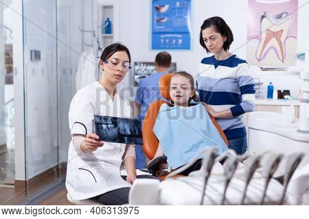 Dentist Examining Little Kid Radiography Sitting On Chair Wearing Dental Bib. Stomatologist Explaini