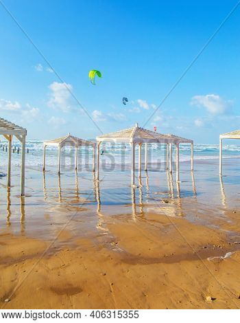 Windy sunny day on the Mediterranean coast. Beach canopies on the sand are illuminated by the setting sun. Embankment in Tel Aviv. Sunset. Winter in Israel.