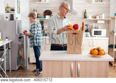 Cheerful Happy Family Healthy Lifestyle Putting Fresh Fruits And Groceries In Refrigerator. Elderly