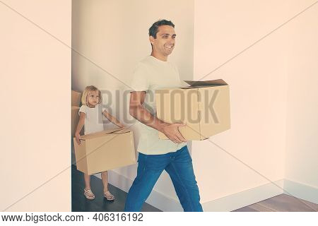 Joyful Father Holding Box, Smiling And Entering Into Room. Lovely Blonde Daughter Going After Dad. H