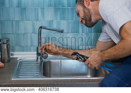 Fix A Leak. Close Up Shot Of Professional Repairman Using Pipe Wrench While Examining And Fixing Fau
