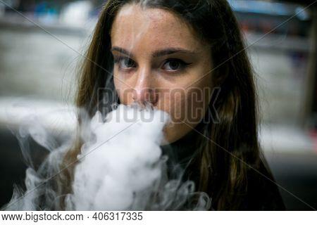 Vaping Teenager. Young Pretty White Caucasian Teenage Girl With Long Hair Smoking An Electronic Ciga