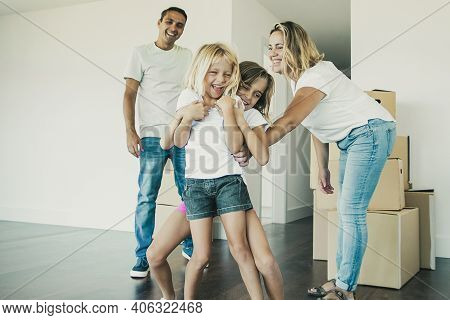 Joyful Family Couple And Two Kids Having Fun While Moving Into New Apartment. Girls Tickling Each Ot
