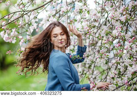 Portrait Of A Beautiful Brunette Young Women In Blue Jacket  In Blossom Apple Tree Garden In Spring