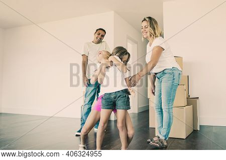 Cheerful Family Couple And Two Kids Having Fun While Moving Into New Apartment. Girls Tickling Each
