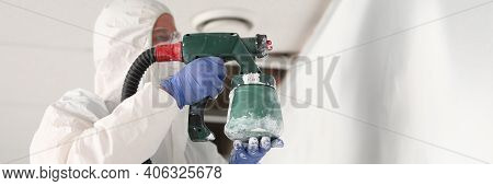 Close-up Of Professional Foreman Holding Spray Gun And Painting Wall In Light Colour. New Apartment