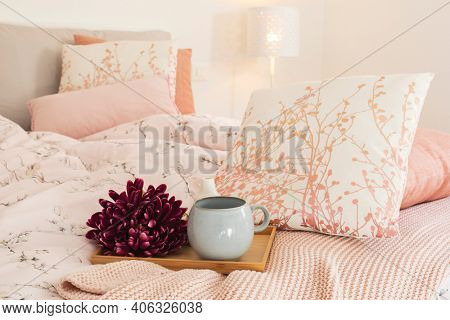 Close up of tray with flower and large cup ready to make breakfast. Tray put on the bed with large, fresh and clean pillows.