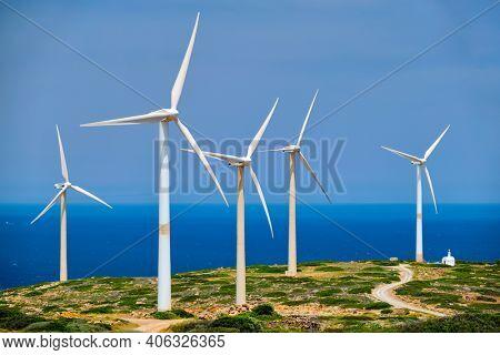 Green renewable alternative energy concept - wind generator turbines generating electricity. Wind farm on Crete island, Greece with small white church