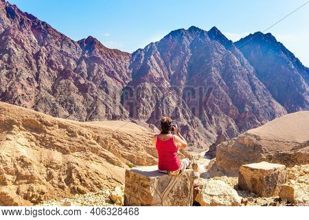 Woman in red T-shirt photographs strange and incredible rocks of red-orange sandstone. The Eilat Mountains. Israel. Multicolored landscape formations