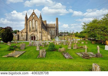 View Of St Canice's Cathedral, A Mediaval Religious Monument Of Kilkenny In Ireland Made Of Grey Sto