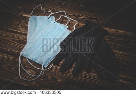 Medical Masks And Black Medical Rubber Gloves On A Wooden Background. Covid-19 Virus Protection Conc