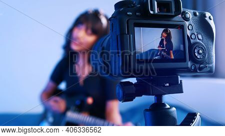 Young Woman Playing Guitar In Front Of The Camera. Recording Demo Or Giving Online Class. High Quali