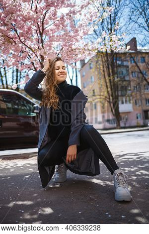 A Young Slender Female Model With Long Wavy Hair And, Dressed In A Gray Coat, Sneakers, Sits On The