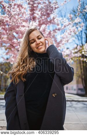 A Young Slender Female Model With Long Wavy Hair And, Dressed In A Gray Coat, Sneakers, Stands On Th