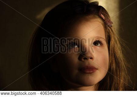 Little Girl In Dark Side With Shadow On Face With Blissful Eyes  Looking Up Dreaming Or Praying