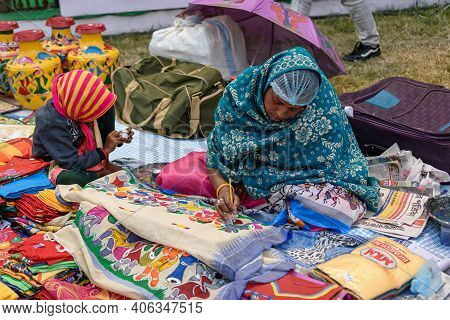 An Indian Unidentified Middle-aged Woman Paints On Colourful Handicraft Items For Sale In Kolkata In