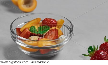 Berry And Fruit Salad Of Strawberries And Apricots In A Bowl Close-up. Near The Bowl Are Scattered A