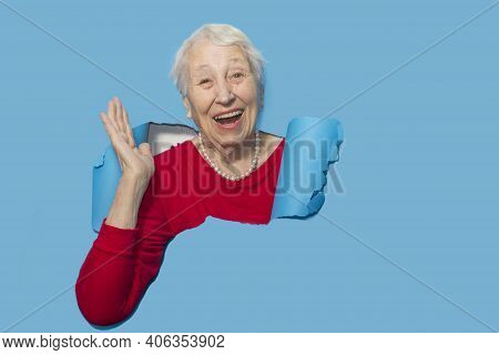 Surprised Woman Looking Through Hole In Paper Wall.