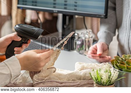 Man With Credit Card Buying Gift In A Female Clothing Store. Woman Cashier Scanning Price Tag Using