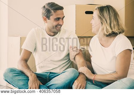Caucasian Couple Relaxing During Relocation And Looking At Each Other. Happy Home Buyers Sitting Cro