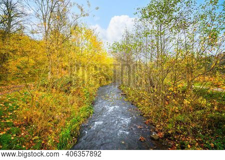 Autumn Scenery With A River Stream Going Through A Colorful Forest In The Fall