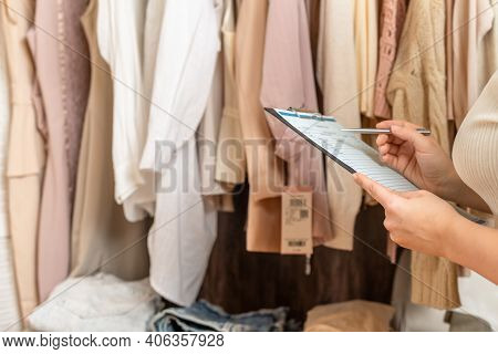 Female Entrepreneur Holding A Clipboard With Inventory List While Doing Inventory In Her Trendy Clot