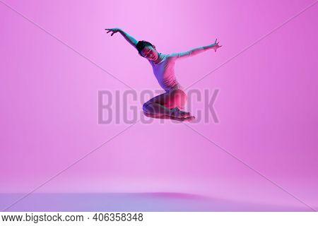 Flying, Jumping. Young And Graceful Ballet Dancer On Pink Studio Background In Neon Light. Art, Moti