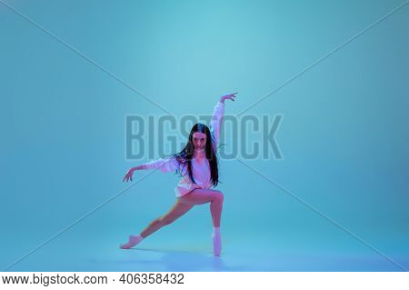 Strong. Young And Graceful Ballet Dancer Isolated On Blue Studio Background In Neon Light. Art, Moti