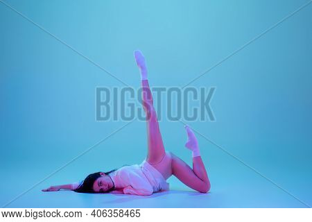 Look. Young And Graceful Ballet Dancer Isolated On Blue Studio Background In Neon Light. Art, Motion