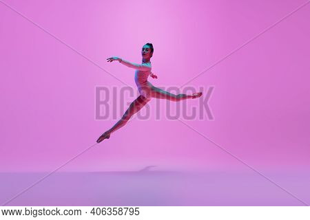 Beautiful. Young And Graceful Ballet Dancer On Pink Studio Background In Neon Light. Art, Motion, Ac