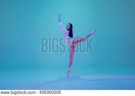 Art. Young And Graceful Ballet Dancer Isolated On Blue Studio Background In Neon Light. Art, Motion,