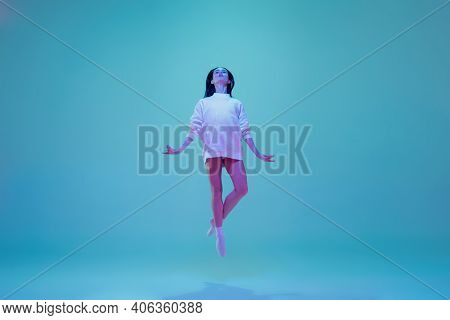 In Flight. Young And Graceful Ballet Dancer Isolated On Blue Studio Background In Neon Light. Art, M